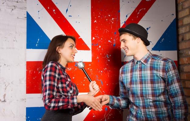 英国の旗のプリントの前でトレンディなファッションのゲストと握手マイクを持つ幸せなインタビュアー女性。