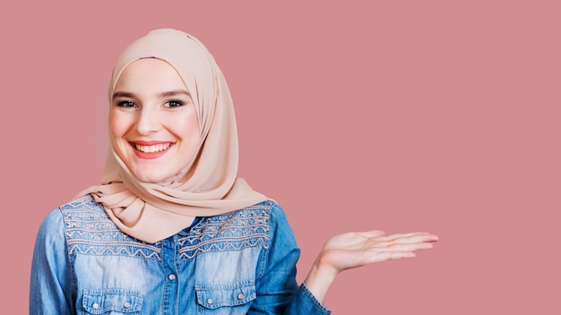 Happy islamic woman presenting something on background