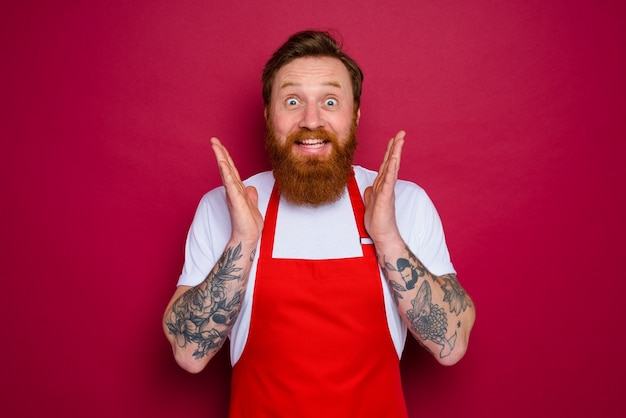 Happy isolated chef with beard and red apron