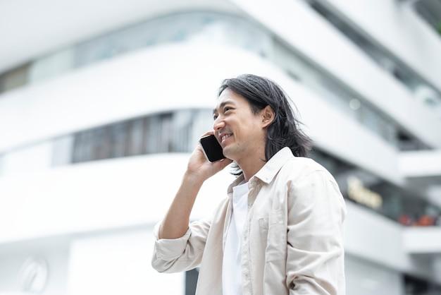 彼のスマートフォンで話している幸せな日本人男性