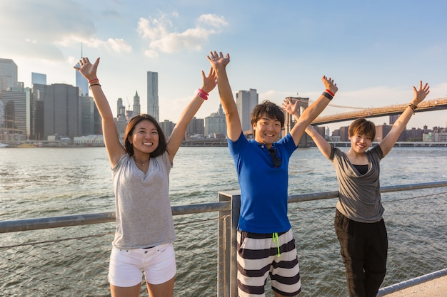 Happy japanese tourists with raised arms in new york