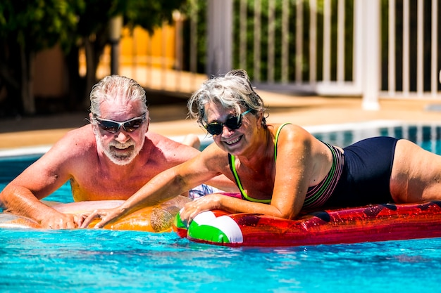 幸せな喜び陽気な人々大人の年配のカップルは、夏休みの休暇のライフスタイルのためにホテルリゾートの青い海にトレンディな色のリロスマットレスと一緒にプールで楽しんでいます