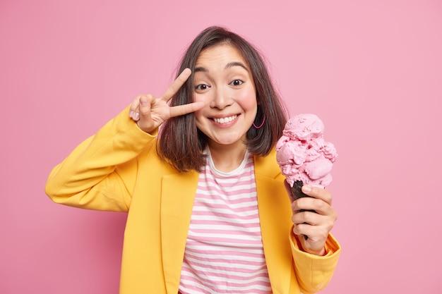 幸せなうれしそうなアジアの女性は、ピンクの壁に隔離された暑い夏の日の間にスタイリッシュな服を着たワッフルで歯を見せて大きなコーンアイスクリームを持って笑顔で勝利のサインを作ります。