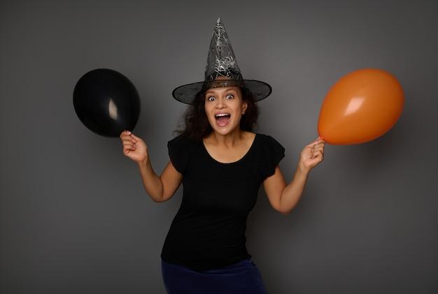 魔法使いの帽子をかぶって、幸せで楽しい美しいヒスパニック系の女性は、オレンジ色と黒の色の2つのエアボールを保持し、コピースペースで灰色の背景にポーズをとってカメラを見ています。ハロウィーンのコンセプト