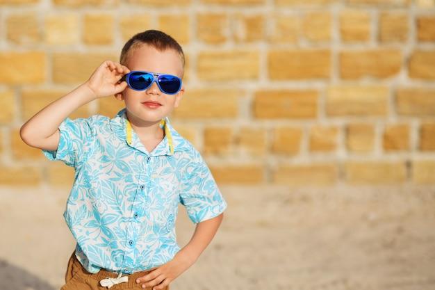 Счастливый радостный красивый маленький мальчик в синих зеркальных солнцезащитных очках