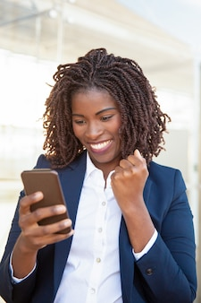Happy joyful business woman holding cellphone
