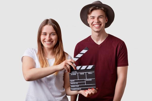 幸せなうれしそうなカップルが近くに立って、カチンコを前に持って、次のシーンの準備をして、白で隔離され、映画館で肯定的な感情を表現します。スレート映画、映画制作