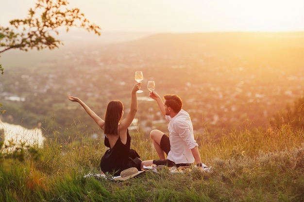 Happy joyful couple with hands up enjoy view and beautiful sunset at summer picnic.