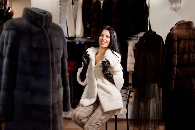 모피 가게에서 흰색 밍크 코트에 포즈 행복 즐거운 소녀