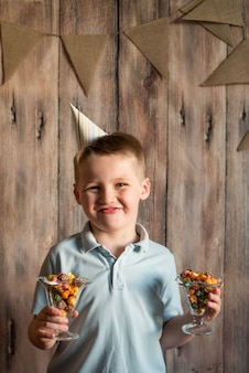 Счастливый радостный смех маленький мальчик на вечеринке. содержит красочный попкорн в стакане.