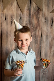 Happy joyful laughing little boy at a party. holds a colorful popcorn in a glass. on a wooden background with flags