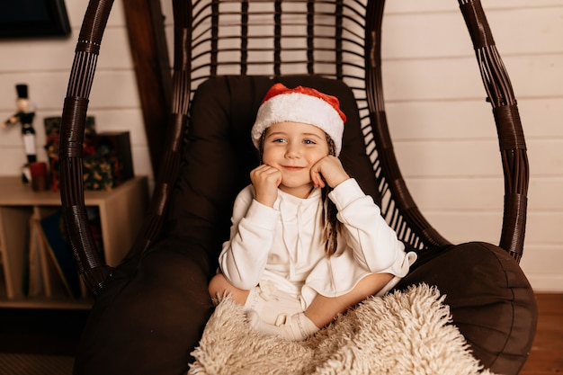 Happy joyful little girl wearing santa costume posing at home and waiting for christmas presents
