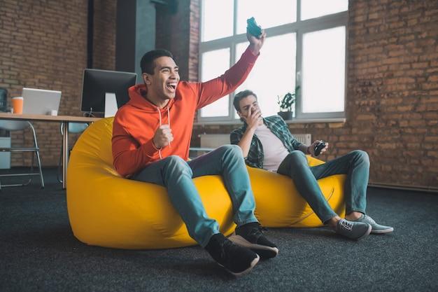Счастливый радостный мужчина держит игровую консоль, будучи счастливым из-за своей победы