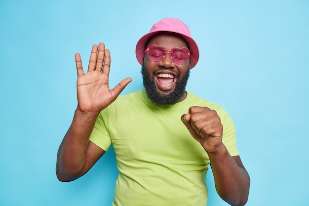 Happy joyful man raises palm sings song keeps hand near mouth as if microphone has upbeat mood wears casual green t shirt pink panama trendy sunglasses isolated over blue wall