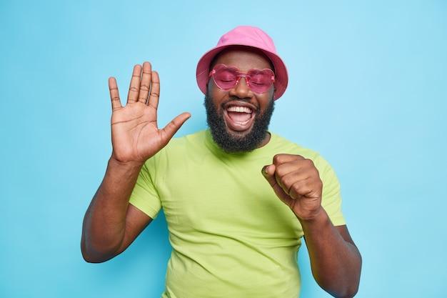 幸せなうれしそうな男が手のひらを上げて歌を歌うマイクが明るい気分を持っているかのように手を口の近くに保つカジュアルな緑のtシャツピンクのパナマ流行のサングラスを青い壁に隔離