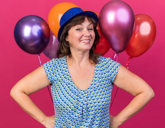 Felice e gioiosa donna di mezza età con cappello da festa che tiene palloncini colorati che sorride allegramente celebrando la festa di compleanno in piedi sul muro rosa