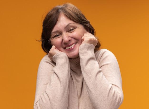Felice e gioiosa donna di mezza età in dolcevita beige con le mani sulle guance in piedi sopra la parete arancione