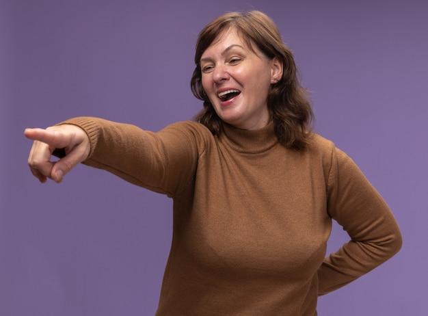 Felice e gioiosa donna di mezza età in dolcevita marrone che guarda da parte indicando con il dito indice a qualcosa in piedi sopra il muro viola