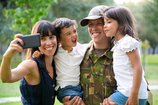 Famiglia militare gioiosa felice che celebra il ritorno di papà, godersi il tempo libero nel parco, prendendo selfie sullo smartphone. colpo medio. ricongiungimento familiare o concetto di ritorno a casa