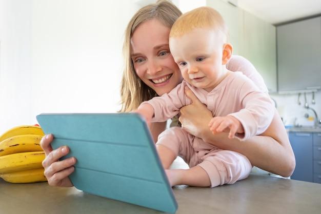 幸せなうれしそうなママと赤ちゃんの娘が台所で家族と話し、タブレットをビデオ通話に使用して、画面で一緒に笑っています。育児やオンラインコミュニケーションの概念