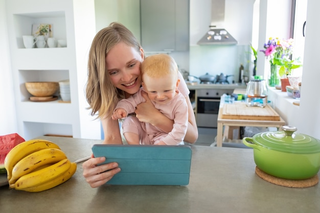 Happy joyful mom and baby daughter watching online recipes, using tablet in kitchen, smiling at screen together. child care or cooking at home concept