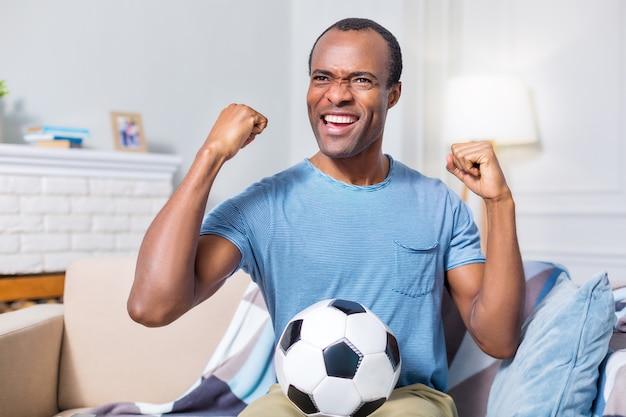 Счастливый радостный приятный мужчина улыбается и держит мяч, будучи футбольным фанатом