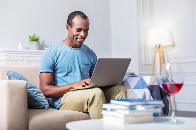 Счастливый радостный приятный человек улыбается и использует ноутбук, сидя на диване
