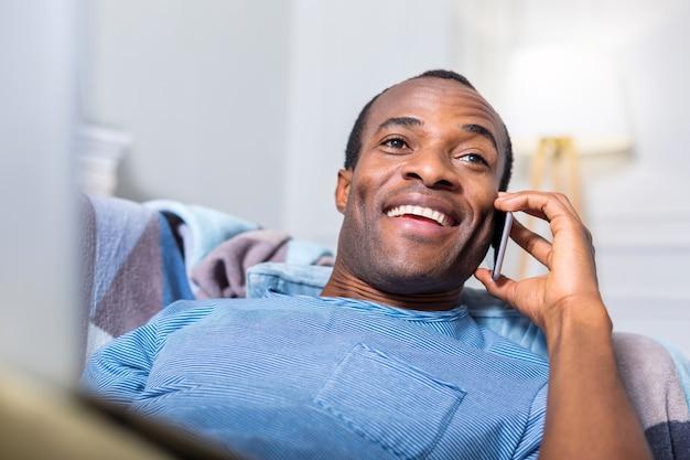 Счастливый радостный позитивный человек, лежащий на диване и улыбающийся во время разговора по телефону