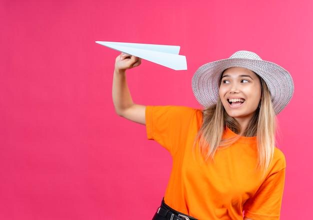 Una bella giovane donna felice e gioiosa in una maglietta arancione che indossa cappellino da sole sorridente mentre vola aeroplano di carta su una parete rosa