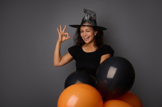 幸せなうれしそうな笑顔の歯を見せる笑顔ハロウィーンパーティーの魔女のカーニバルの衣装を着たウィザードの帽子をかぶったヒスパニック系の女性は、okのサインを示し、黒い風船で灰色の背景にポーズをとる、コピースペース