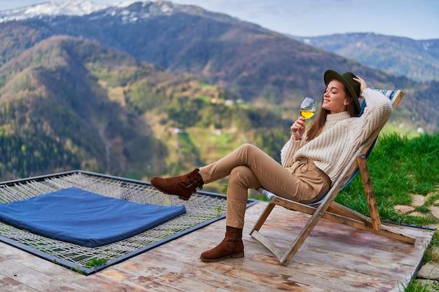 Счастливая радостная улыбающаяся спокойная безмятежная женщина-хипстер-путешественница, сидящая на шезлонге с бокалом вина, наслаждаясь путешествием и спокойным отдыхом