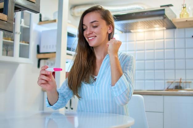 赤ちゃんを夢見ている幸せなうれしそうな笑顔の女性は、自宅での陽性妊娠検査で喜ぶ