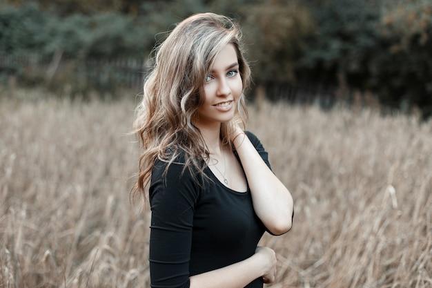 가을 날에 옥수수 밭에 포즈 유행 검은 티셔츠에 아름다운 미소로 행복 즐거운 세련된 현대 젊은 여성 모델