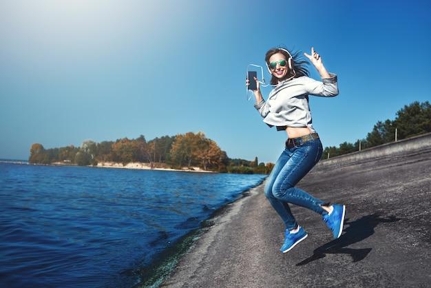 Счастливая радостная женщина слушает музыку, находясь на открытом воздухе у моря
