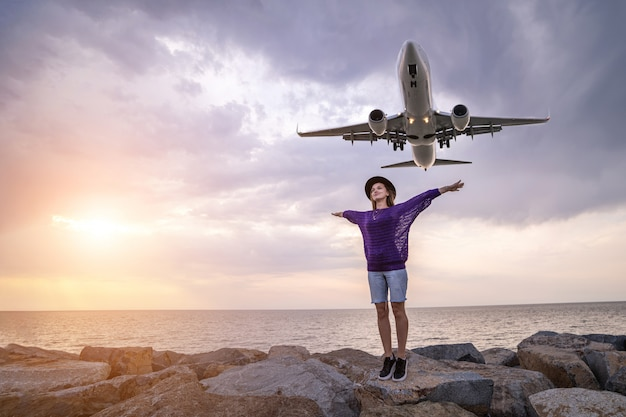 Happy joyful woman traveler in hat stands on stones against sea feeling carefree freedom with open arms and enjoying flying passenger airplane
