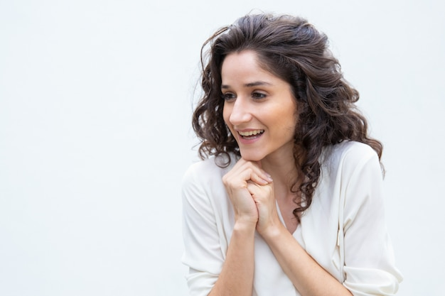 Счастливая радостная женщина со сложенными руками смотрит в сторону