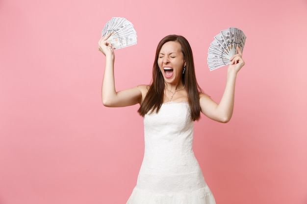Happy joyful woman with closed eyes in white dress hold bundle lots of dollars, cash money screaming