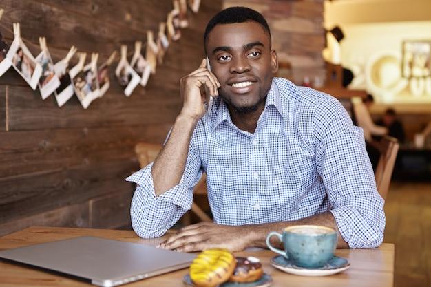 彼の妻に携帯電話で話している幸せなうれしそうな若いアフリカ系アメリカ人実業家