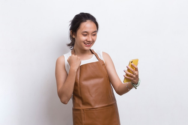Happy joyful young asian woman bartender or waitress using mobile smartphone on white background