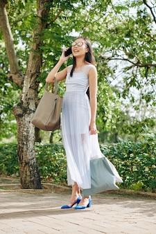 도시 공원에 섬유 가방을 들고 서서 친구나 가족과 전화 통화를 하는 sunglsses를 입은 행복한 젊은 아시아 여성