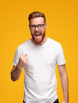 Счастливый радостный молодой бородатый мужчина в белой футболке и очках сжимает кулак и кричит, празднуя победу на желтом фоне