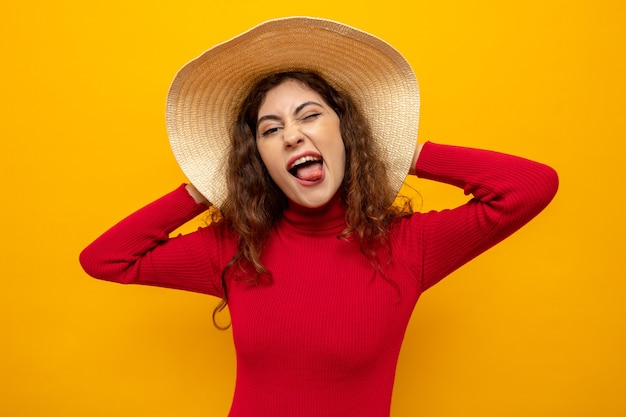 Happy and joyful young beautiful woman in red turtleneck in summer hat looking at front having fun sticking out tongue standing over orange wall