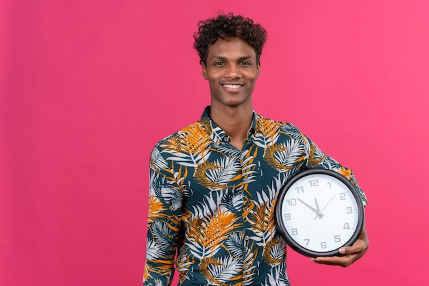 Happy and joyful young dark-skinned man with curly hair in leaves printed shirt holding wall clock showing time
