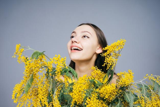 노란색 향기로운 미모사를 들고 웃고 있는 행복한 즐거운 어린 소녀