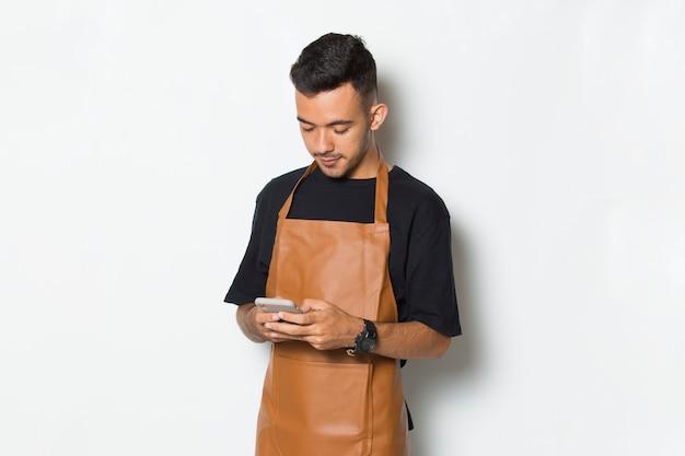 Happy joyful young man barista waitress using mobile smartphone isolated on white background