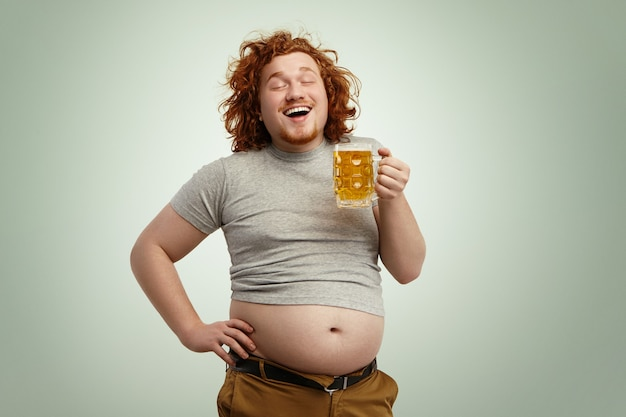 Happy joyful young overweight man with curly red head closing eyes in enjoyment