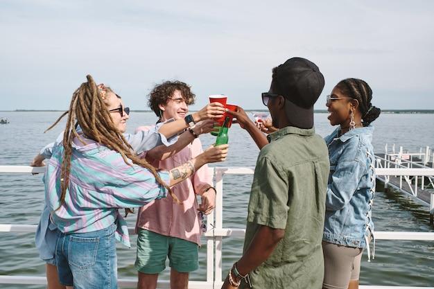 부두에서 작은 파티를 할 때 안경과 맥주 병으로 건배하는 행복한 즐거운 젊은이들