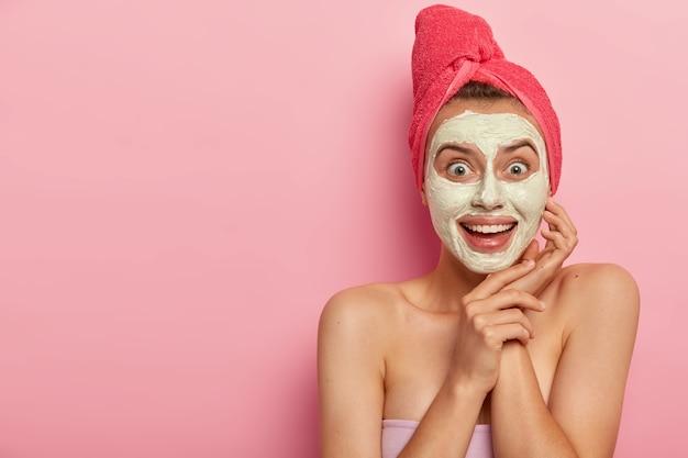 Felice gioiosa giovane donna applica una crema maschera meravigliosa per qualsiasi tipo di pelle, indossa un asciugamano rosso sulla testa, nutre la pelle, ha un aspetto positivo