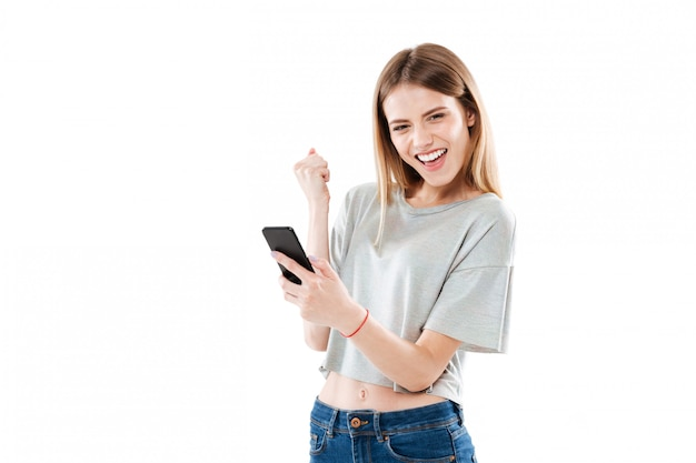 Happy joyful young woman holding mobile phone and celebrating a win