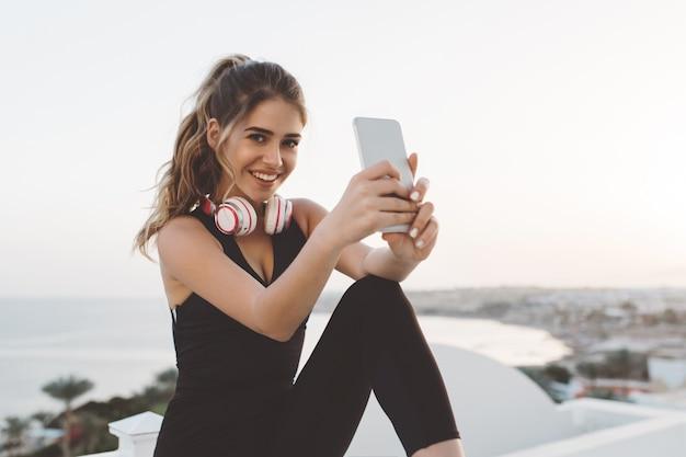 행복 한 즐거운 젊은 여자 매력적인 운동복 전화, selfie를 만드는 웃 고, 바닷가에 아침에 일출을 즐기고. 쾌활한 분위기, 진정한 행복
